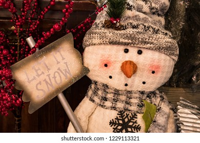 Toy Snowman Wearing a Hat and Scarf holding a sign saying Let it Snow.