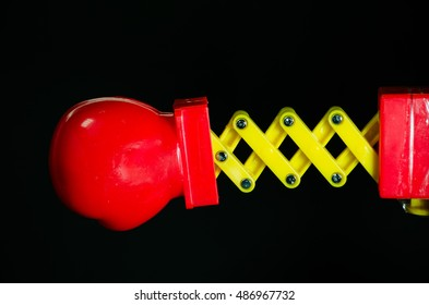 Toy Spring Boxing Glove Punch on Black Background