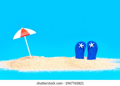 Toy sun umbrella and flip flops in the sand on blue background. Creative beach vacations concept.
