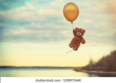 Toy teddy bear flying on a yellow balloon. Flight over the lake. Cartoon character. Birthday. Present. Balloon.