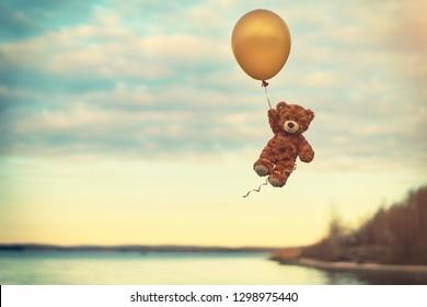 Toy teddy bear flying on a yellow balloon. Flight over the lake. Cartoon character. Birthday. Present. Balloon.
