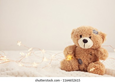 Toy teddy bear on soft plaid background with beautiful Christmas lights. Winter time, holidays, gifts concept.