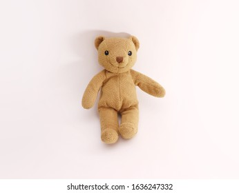 toy teddy bear sitting, isolated on white background