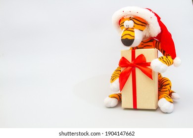 A toy tiger holds a gift in its paws, on a light background, new year, oriental calendar, year of the tiger.