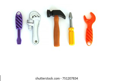Toy tools lined up on white background, flat lay.