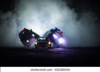 Toy Toyota FJ Cruiser cars chasing a Ford Thunderbird car at night with fog background. Toy decoration scene on table . Selective focus - 11 JAN 2018, BAKU AZERBAIJAN