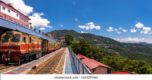 Toy train Kalka-Shimla route, standing on Shimla railway station with city in background. Shimla is state capital & tourist holiday destintation in the hill state Himachal Pradesh, India.