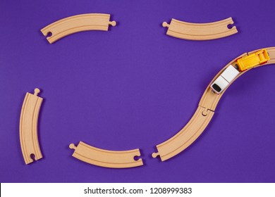 Toy train and wooden rails pieces on blue color background