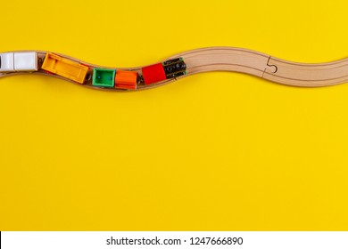 Toy trains and wooden rails on yellow color background