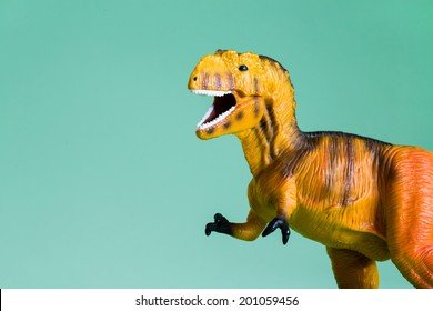 Toy T-Rex on blue/green background