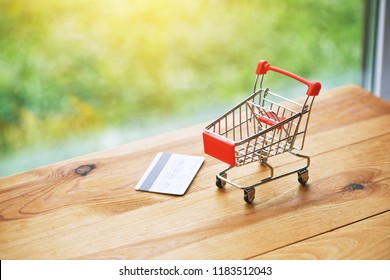 toy trolley with credit card as symbol of shopping and paying