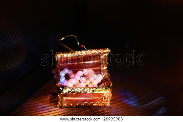 Toy trunk with paste pearl. izobrazhayuschiym valuables. A tab is visible which he is suspended for.