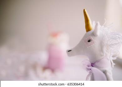Toy unicorn on backgound of pink milk shake. Milk shake, cocktail. Unicorn coffee. Unicorn food. Soft focus
