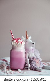 Toy unicorn with pink milk shake with cream, marshmallow and colorful decoration. Milk shake, cocktail. Unicorn coffee. Unicorn food
