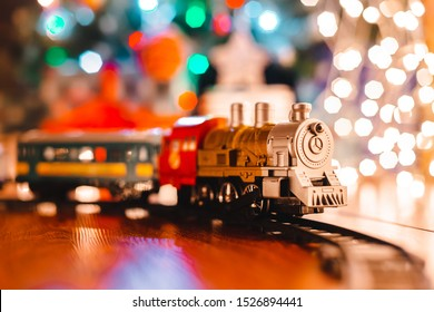 toy vintage steam locomotive on the floor under a decorated Christmas tree on a background of bokeh lights garland. Christmas and New year celebration concept, background. free space