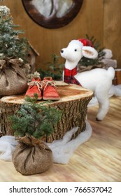 a toy white deer and a wooden stump on the background of the winter house of a Christmas gnome.