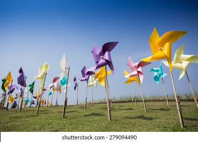 Toy windmill concept of green energy wind farm in field