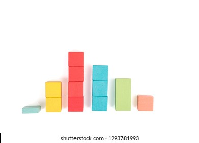Toy wooden blocks as financial graph. Graph with four 4 steps. Growing chart. Infographic diagram, chart over grey or black or dark background. Multi-colored wooden blocks.