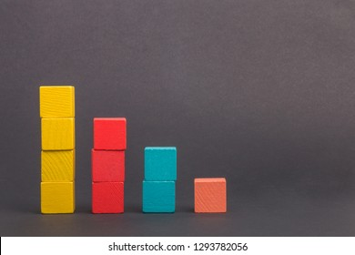 Toy wooden blocks as financial graph. Graph with four 4 steps. Infographic diagram, chart over grey or black or dark background. Multi-colored wooden blocks.