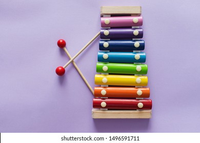 A toy wooden colorful xylophone on purple background with copy space. Children's toy and musical instrument. Music and childhood concept.