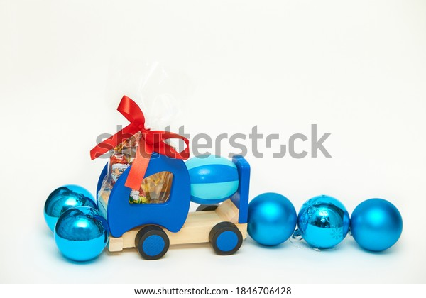 Toy wooden concrete mixer truck. Children's toy with Decorative red bow and blue Christmas ornament. Gift for kids.
