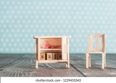 """Toy wooden cupboard with word """"Sale"""" and pink flowers  and chair on a table in nursery room"""