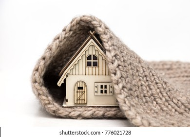 toy wooden house wrapped in a warm knitted scarf on a white background