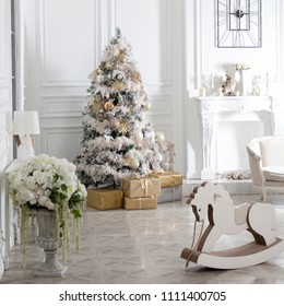 Toy wooden rocking horse in the New Year's interior. New Year's decorations. Decoration of the house. White wooden rocking horse. Christmas interior