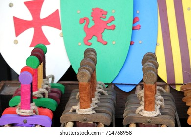 Toy wooden swords and shields for sale in a toyshop, for boys to play medieval battles