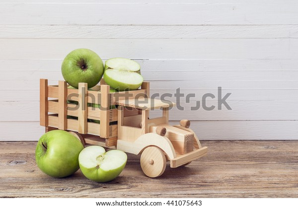 Toy wooden truck with green apples in the back. Place for text.