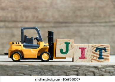 Toy yellow forklift hold letter block J to complete word JIT (Abbreviation of Just in time)on wood background
