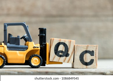 Toy yellow forklift hold letter block Q to complete word QC (Abbreviation of Quality Control)on wood background