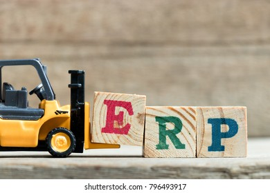 Toy yellow forklift hold letter block E to complete word ERP (Abbreviation of Enterprise Resource Planning)on wood background