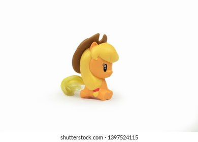 Toy yellow pony in in the slap with a yellow mane on a white background