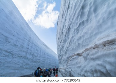 TOYAMA , JAPAN - April 30, 2017:People are walking at the road between snow wall of  Tateyama Kurobe Alpine Route or Japanese Alps with blue sky  background in Toyama Prefecture, Japan.