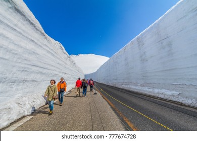 TOYAMA , JAPAN - April 30, 2017:People are walking at Tateyama Kurobe Alpine Route the snow mountains wall at Kurobe alpine , Beautiful landscape with blue sky background. Toyama city, Japan.