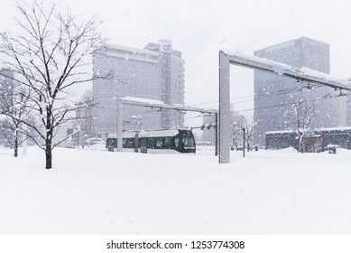 TOYAMA, JAPAN - FEBRUARY 13, 2018: The modern black tram coming to platform of Toyama Station on snowy day in winter. Transportation in Japan. Asia.