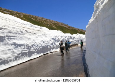 Toyama Japan - May 20, 2017: the tourists bus move along the japan alps snow wall with blue sky background.,Tateyama Kurobe Alpine Route with beautiful landscape snow mountains.,Toyama city, Japan.