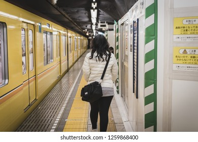 Toyko, Japan - April 13, 2017: Woman walking alongside the platform of a metro station in Tokyo, Japan with yellow metro train stopping. The train was operated by Tokyo Metro.
