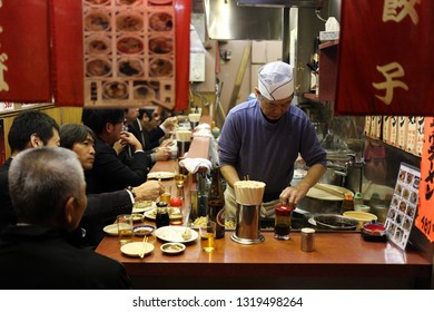 TOYKO, JAPAN - DECEMBER 05, 2016: Unidentified japanese chef preparing the dishes for his clients in a restaurant in Shinjuku area in Toyko, Japan