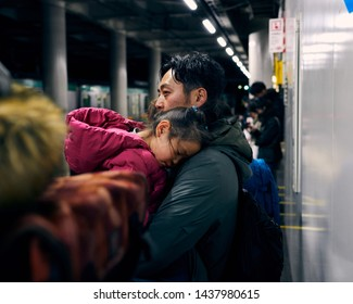 Toyko, Japan - January 4th, 2019. A father holds his sleeping daughter while waiting for a train in Tokyo.