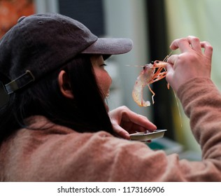 Toyko, Japan - June 6, 2017: A woman about to enjoy some fresh seafood at the fish market in Tokyo, Japan.