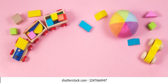 Toys background. Baby kids toys frame with toy cars, colorful wooden cubes on pink background