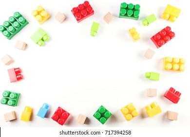 Toys background. Colorful wooden cubes and plastic construction blocks frame on white background.