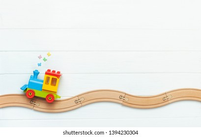 Toys background with copy space. Kids toy train on railway on white wooden background with blank space for text. Top view, flat lay.