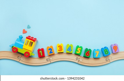Toys background with copy space. Kids toy train with numbers on toy wooden railway on light blue background with blank space for text. Top view, flat lay.