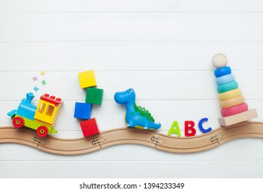 Toys background with copy space. Kids toys train, cubes, dinosaur, ABC letters and pyramid on toy wooden railway on white wooden background with blank space for text. Top view, flat lay.