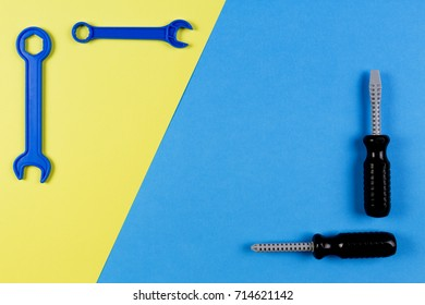 Toys background. Kids construction toys tools - colorful screwdrivers, screws and nuts on blue and yellow background.