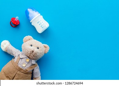 Toys for newborn baby set with teddy bear and milk in bottle on blue background flat lay space for text