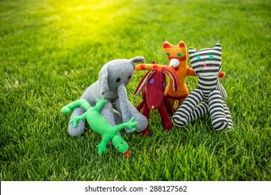 Toys on green grass, focus on dug, elephant, lizard